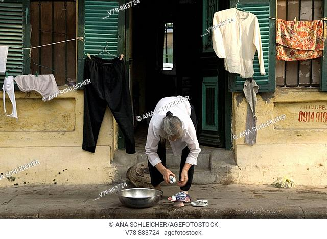 An old woman washing up the tea mugs on the street by her doorway, where her clothes are also getting dried. It is a traditional old house of Hanoi