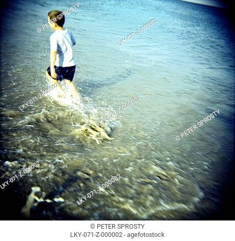 Young boy runs in shallow water