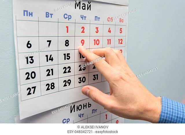 Office worker's hand indicates May holidays on a wall calendar sheet
