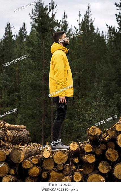Man with camera standing on stack of wood