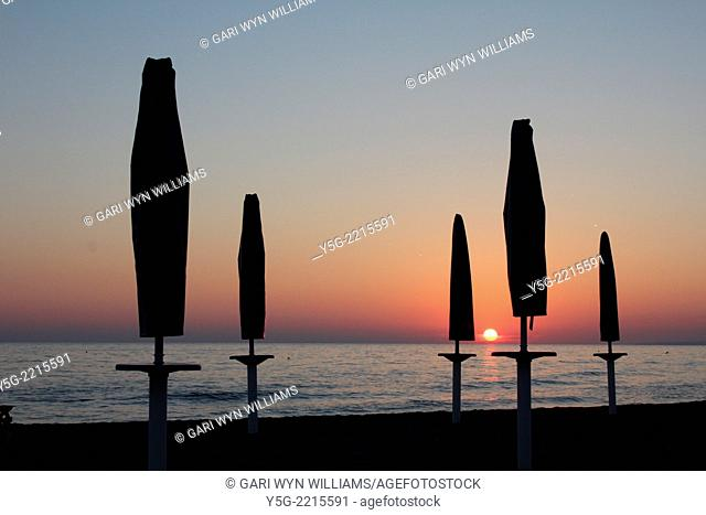 closed umbrellas on beach by the tyrrenhian sea in italy
