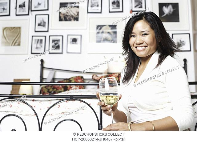 Portrait of a young woman holding a glass of wine smiling
