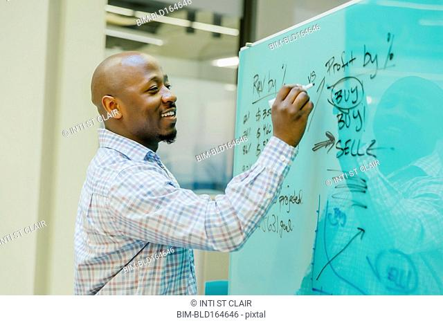 Black businessman writing on whiteboard