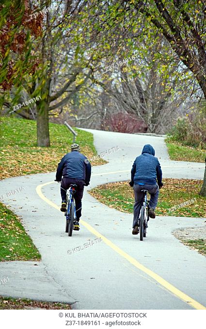 Two cyclists on a winding path in a public park on an autumn afternoon, Ontario, Canada