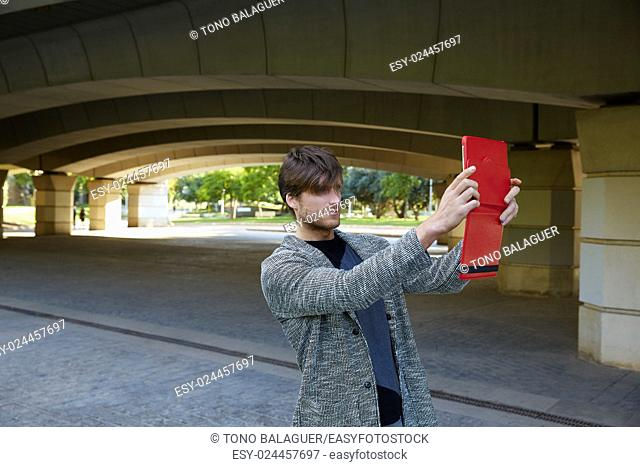 Modern young man with tablet pc touch taking photos under a bridge