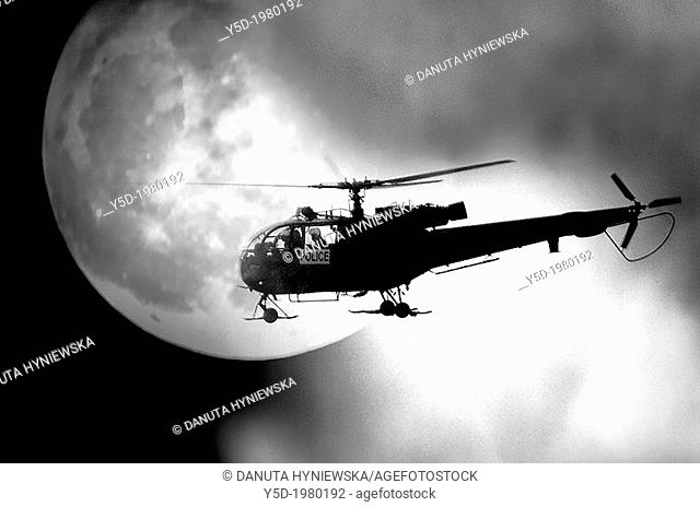 police helicopter against the moon