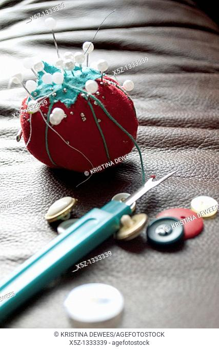 A tomato shaped pin cushion, buttons and seam ripper
