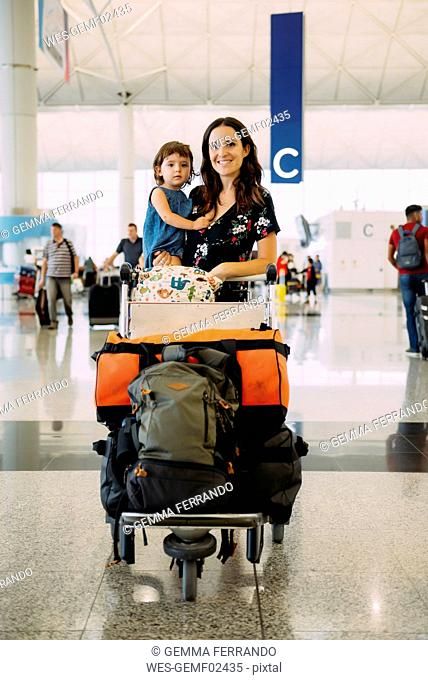 Mother holding a baby girl at the airport and pushing a trolley with the luggage