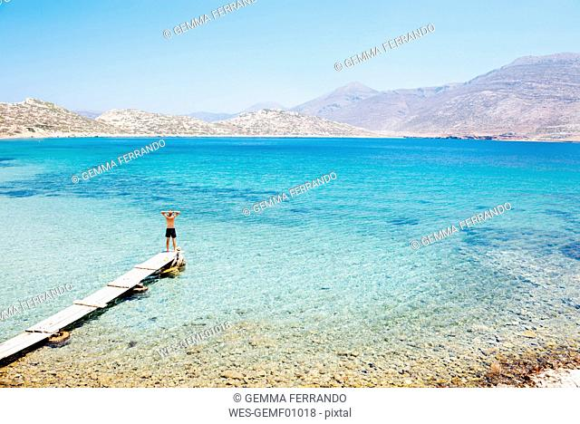 Greece, Cyclades islands, Amorgos, Aegean Sea, man standing on the edge of a wooden dock