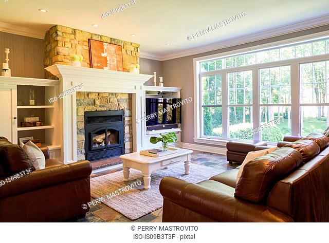 Brown leather sofa, sitting chairs and natural stone fireplace in the living room inside a cottage style home, Quebec, Canada