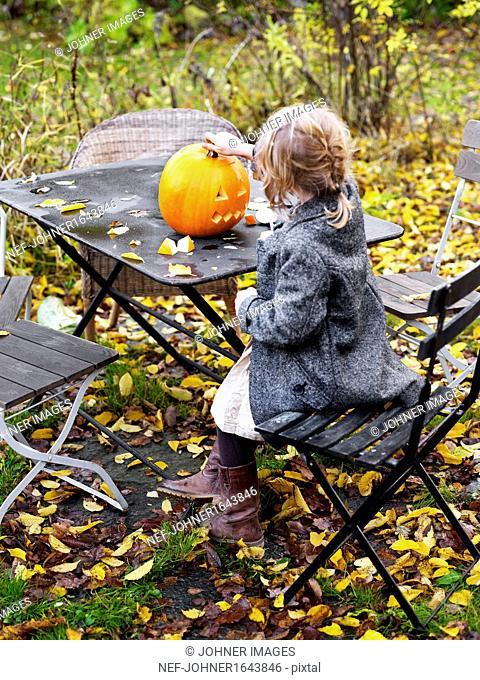 Girl making Jack Olantern outdoors