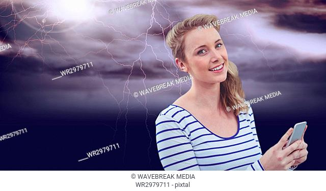 Smiling woman texting in a darkness background