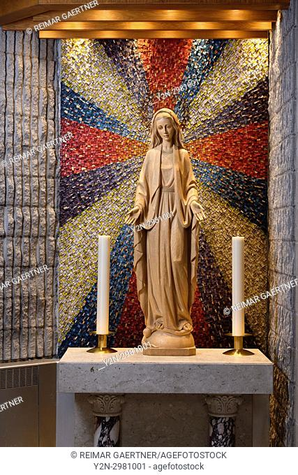 Carved wood statue of Mary Mother of God with 12 star crown standing on moon and serpent at side altar with candles and sunburst mosaic Toronto Ontario Canada