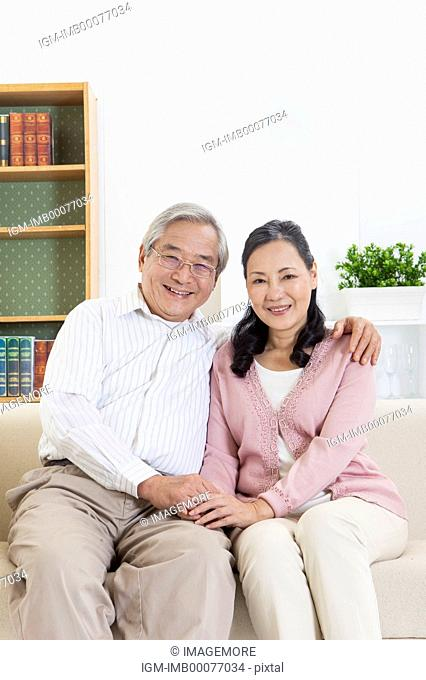Senior couple holding hands and smiling at the camera together