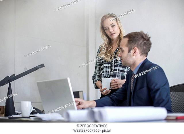 Businessman at desk with colleague looking at laptop