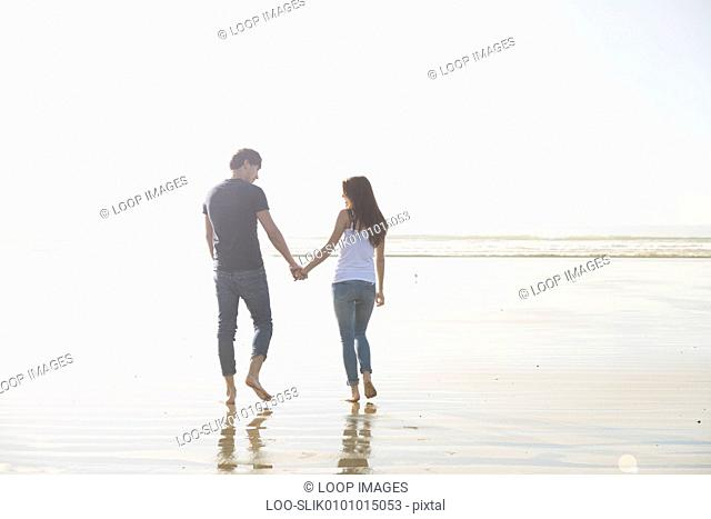 A young couple walk holding hands across the beach at Porthmadog