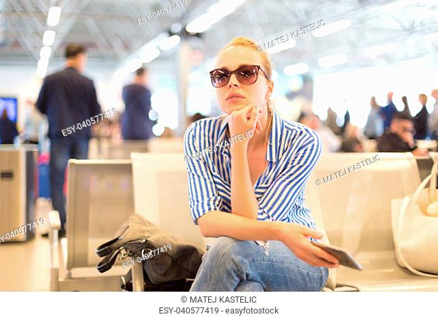 Casual blond young woman using her cell phone while waiting to board a plane at departure gates at international airport