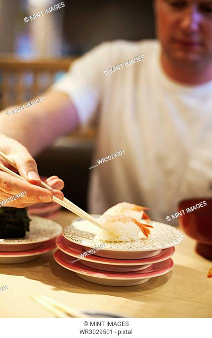Close up of man sitting at table in Asian restaurant, picking up piece of sushi from a plate with chopsticks