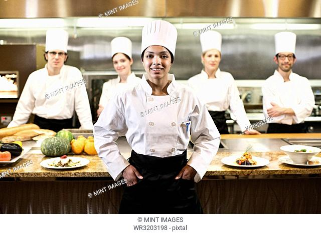 A portrait of a black female chef and her team of chefs in the background of a commercial kitchen