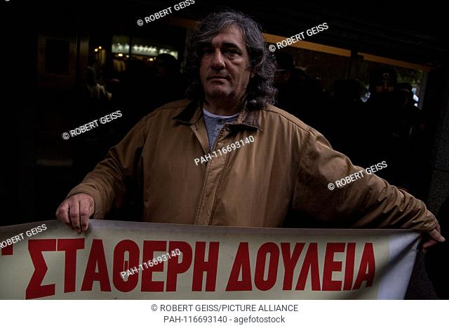 """Greek Employee, during a rally in front of Ministry of Economy, against layoffs. Writing """"""""Permanent work"""""""". 06.02.2019 