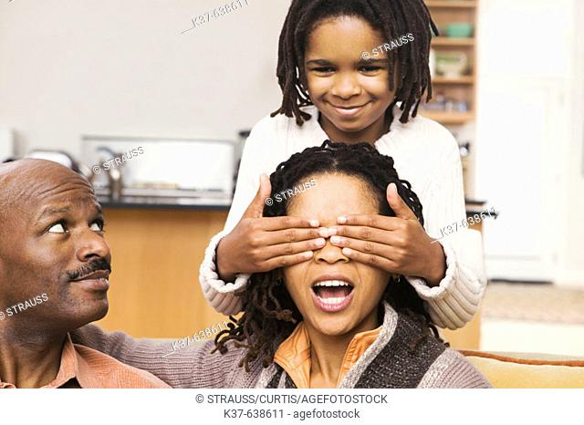 African-American family at home, parents on sofa & daughter covering mother's eyes with hands from behind. Guess who?