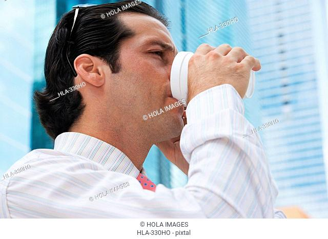 Close-up of a businessman drinking cold drink