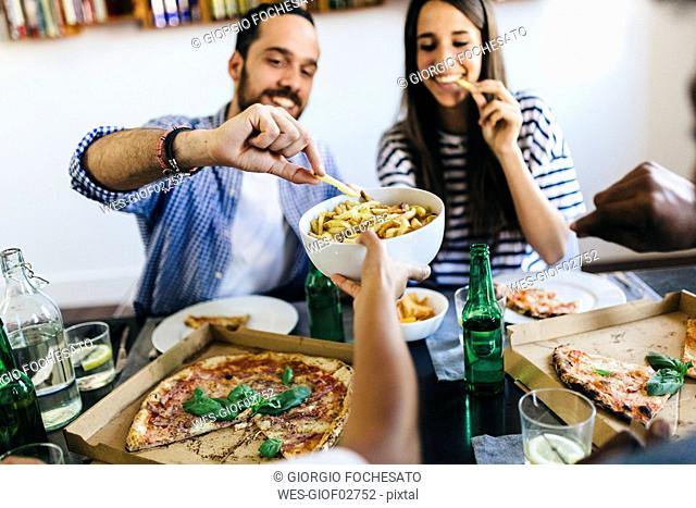 Happy friends having French fries and pizza at home