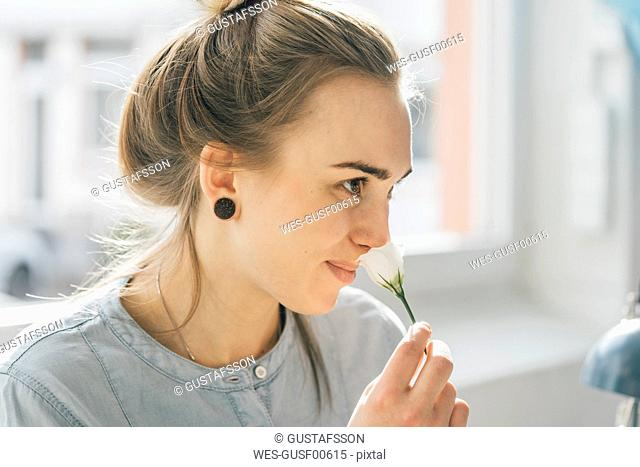 Smiling young woman smelling blossom