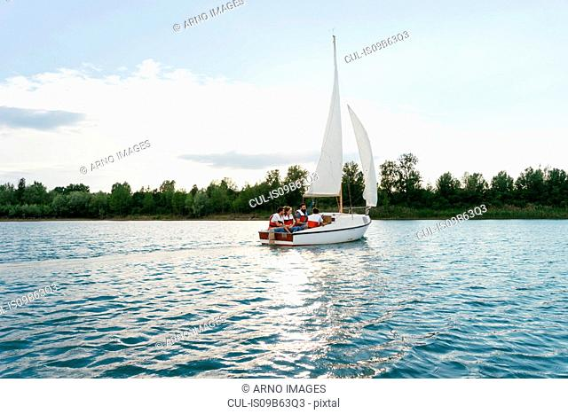 Group of people on sailing boat on lake, Signa, Tuscany, Italy