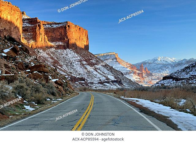 Highway 128 and red rock formations with snow near sunset in winter, Colordao Riverway Recreation Area, Utah, USA