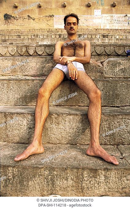 Man relaxing on stairs of ghat , Varanasi , Uttar Pradesh , India