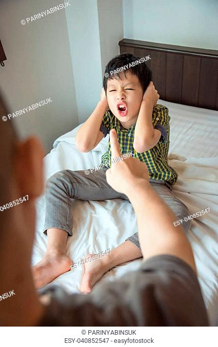 Aggressive asian boy close his ears by hands and shouting to his father on bed at home