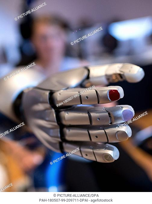 07 May 2018, Germany, Garmisch-Partenkirchen. A worker of the German Aerospace Center presenting the assistant robot EDAN (EMG-controlled daily assistant)
