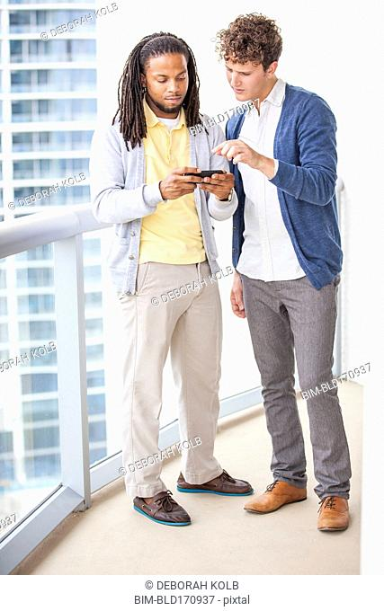 Businessmen using cell phone on urban balcony