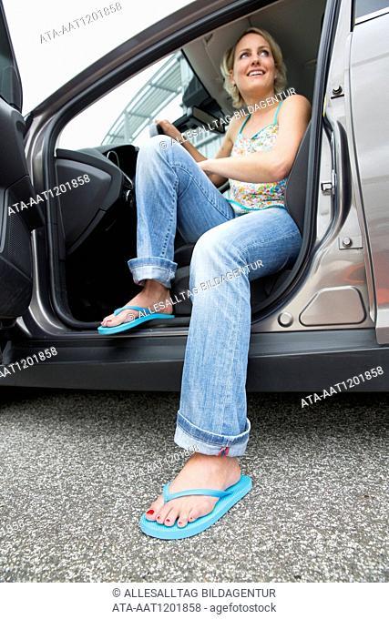 Women drives car with flip-flops