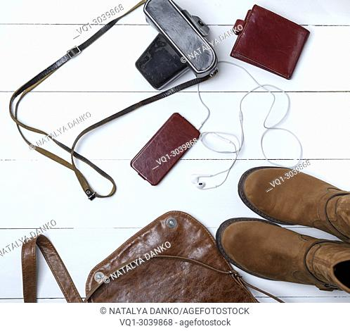 leather brown boots, smartphone in a case with headphones, purse and old vintage camera in a black case with a strap, top view, white wooden background