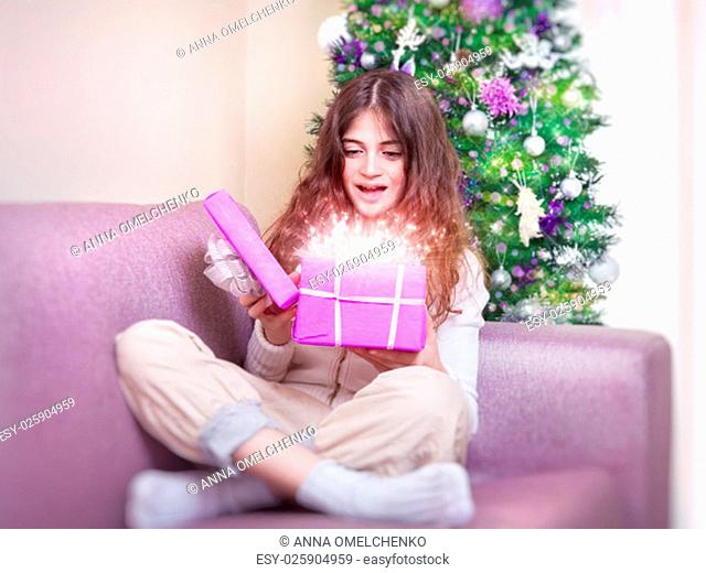 Cheerful teen girl opening gift box with magic glowing present, sitting on the couch near Christmas tree, happy winter holidays