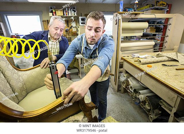 Young Caucasian man learning the art of upholstery from a senior male upholsterer