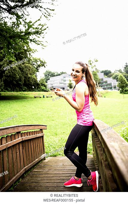 Happy sportive young woman with smartphone and earbuds