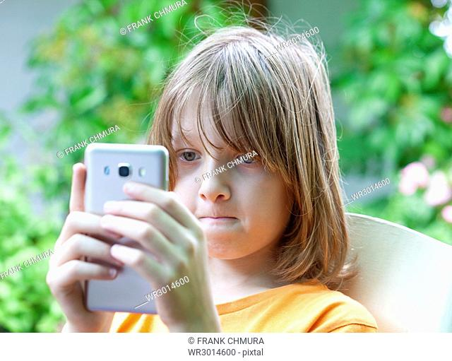 Boy with Blond Hair Looking at Mobile Phone