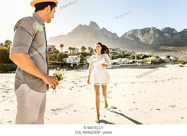 Woman running to boyfriend with flower bouquet on beach, Cape Town, South Africa