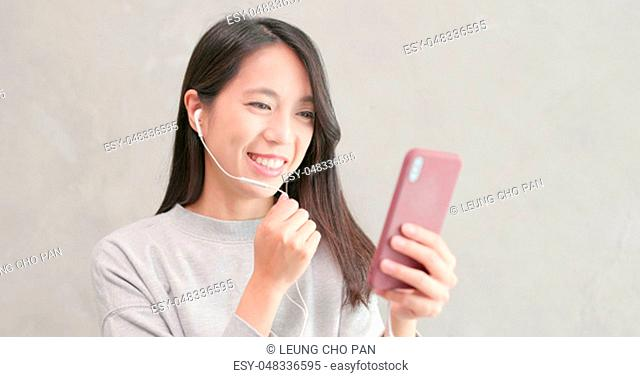 Woman talk to smart phone with earphone