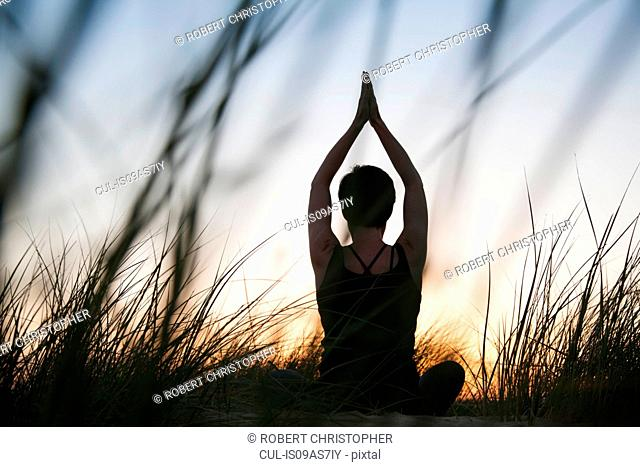 Rear view of mid adult woman practicing yoga in silhouetted long grasses at sunset