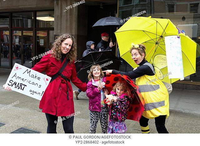 Seattle, Washington: woman dressed in costume as a bee, entertains a family along the route. The March for Science Seattle was a non-partisan rally and sister...