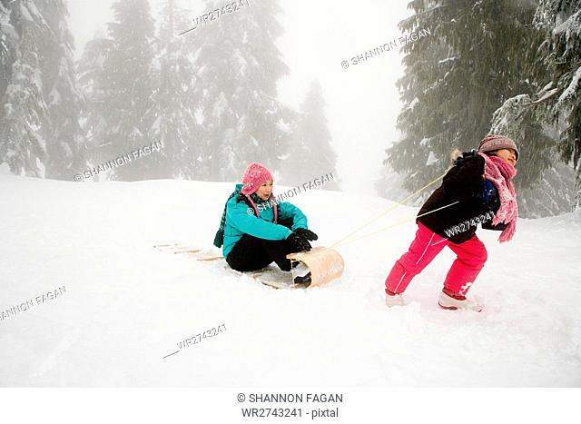 Girl pulling mother on toboggan