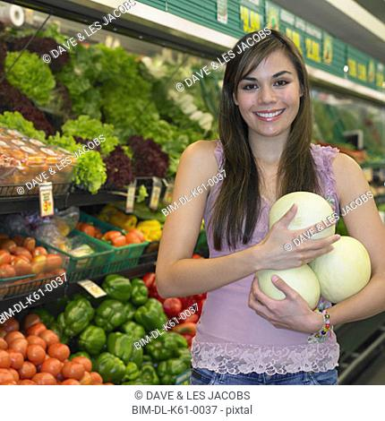 Young woman holding melons in produce section of supermarket, Perth, Australia