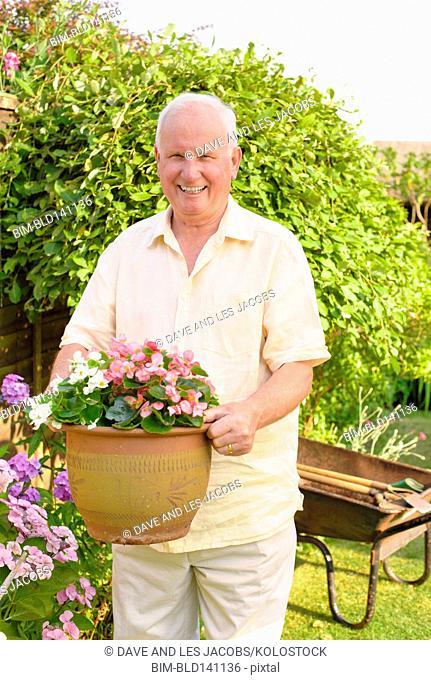 Caucasian man gardening in backyard