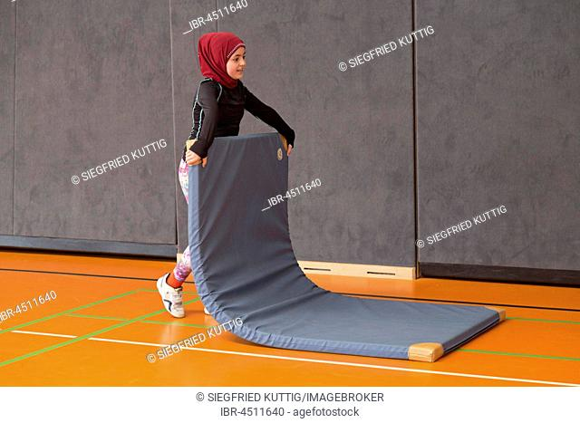 Schoolgirl wearing floor mat, Physical Education, Primary School, Lower Saxony, Germany