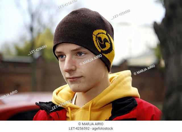 A teenage boy with a cap on his head