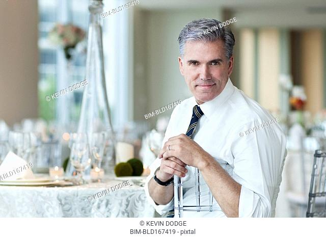 Caucasian businessman smiling in empty dining room